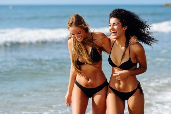 Two young women with beautiful bodies in swimwear on a tropical beach. Funny caucasian and arabic females wearing black bikini walking along the shore.