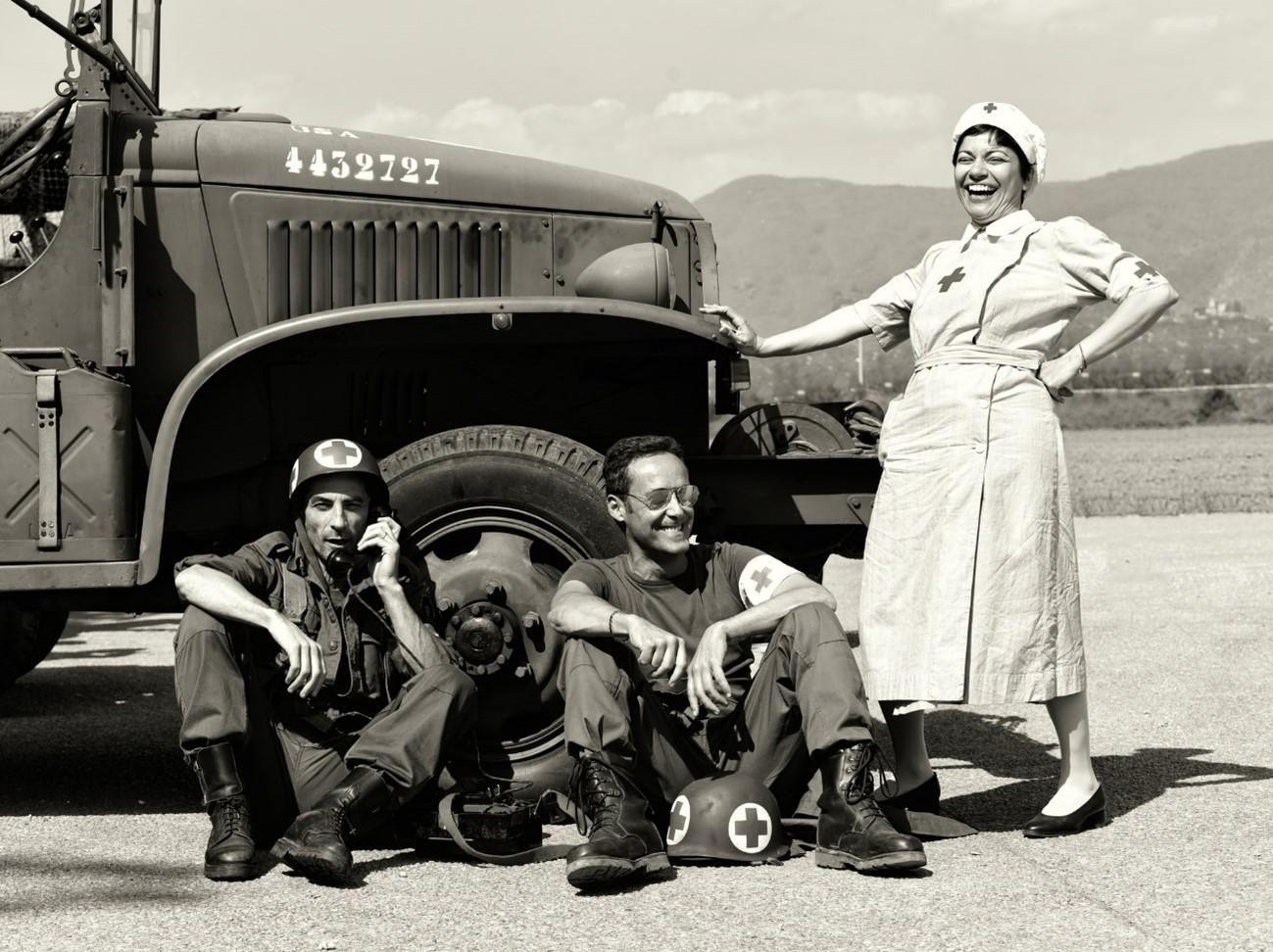 Uma enfermeira sorridente e soldados à frente de um veículo militar da Segunda Guerra Mundial